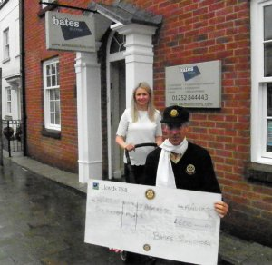 Laura of Bates Solicitors helps push along the Pram Race with a generous sponsorship cheque
